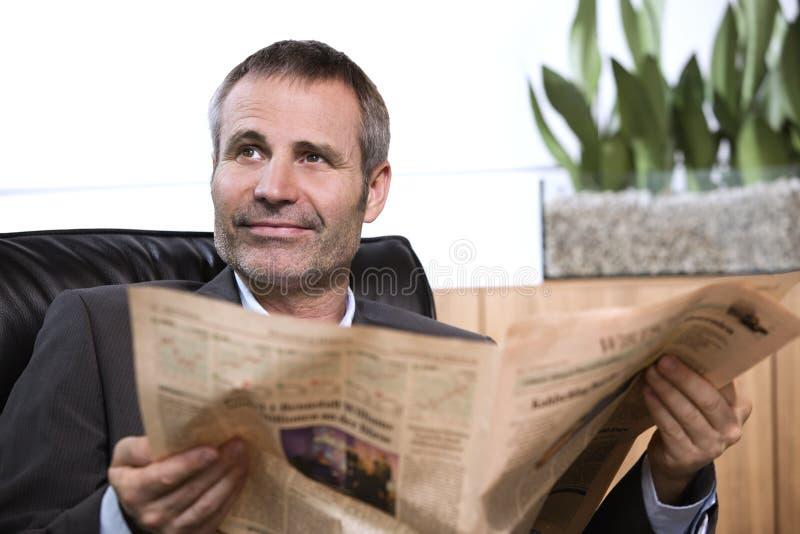 Periódico de la lectura del hombre de negocios y mirada para arriba. foto de archivo