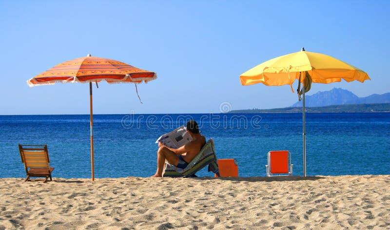 Periódico de la lectura del hombre en la playa imagenes de archivo