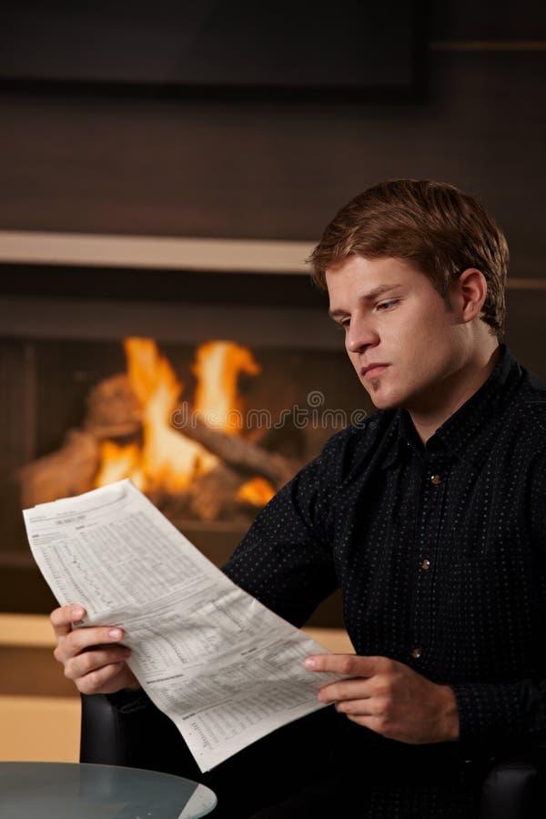 Periódico de la lectura del hombre joven imagen de archivo libre de regalías