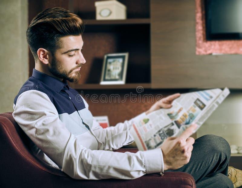 Periódico de la lectura del hombre joven fotografía de archivo