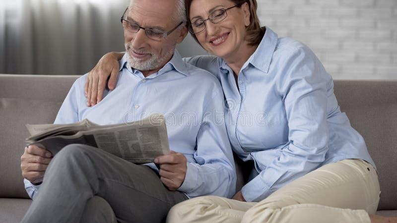 Periódico de la lectura del hombre del jubilado, esposa que pone el brazo alrededor de sus hombros, matrimonio fotos de archivo libres de regalías