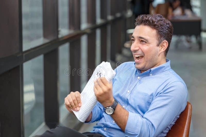 Periódico de la lectura del hombre de negocios sobre el edificio de oficinas Sonrisa feliz del hombre de negocios después de noti imagenes de archivo
