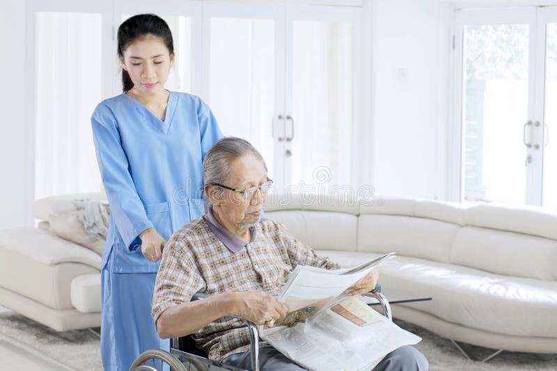Periódico de la lectura del viejo hombre con su enfermera imagen de archivo libre de regalías