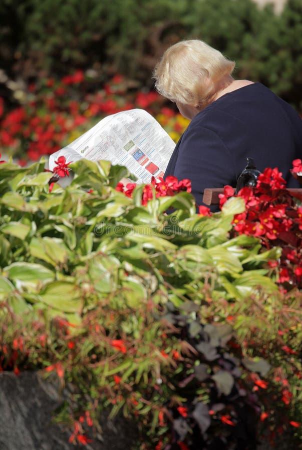 Periódico de la lectura en el parque foto de archivo libre de regalías