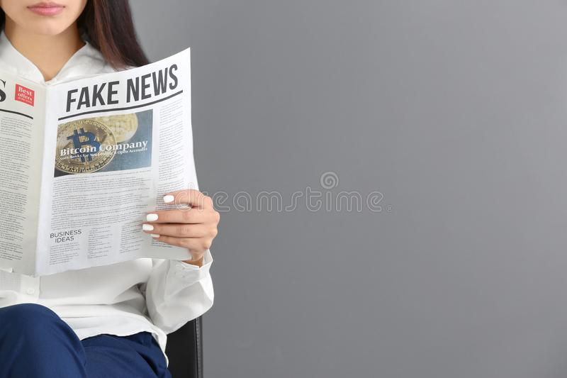 Periódico de la lectura de la mujer joven contra fondo gris fotos de archivo libres de regalías