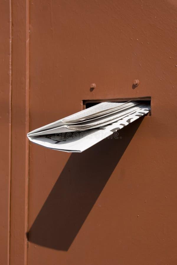 Periódico entregado en puerta roja imágenes de archivo libres de regalías