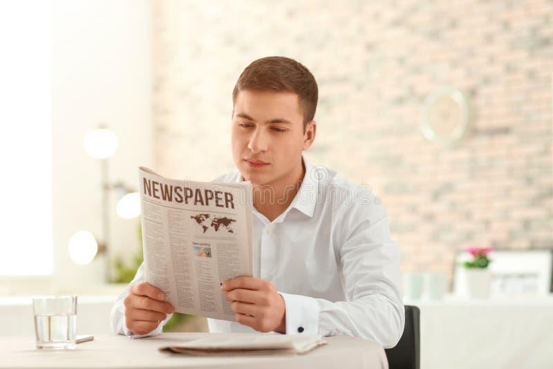 Periódico hermoso de la lectura del hombre joven en café imágenes de archivo libres de regalías