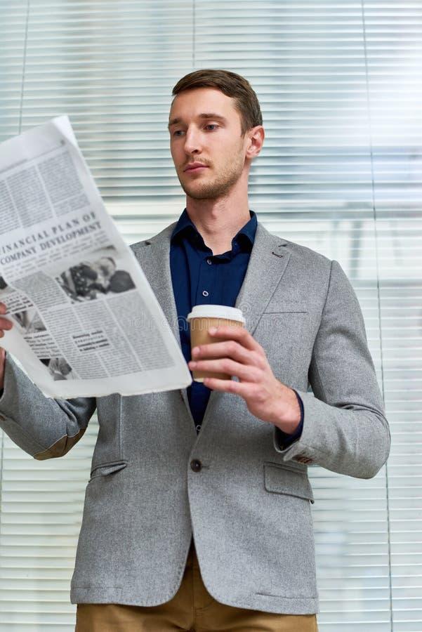 Periódico hermoso de la lectura del hombre joven en oficina imagenes de archivo