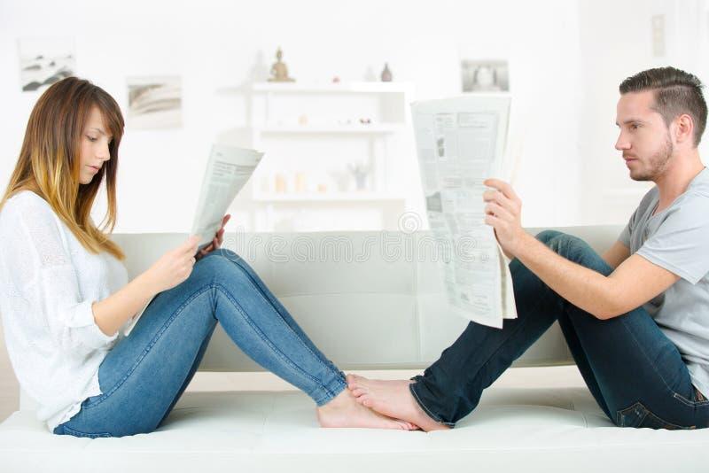 Periódico joven de la lectura de los pares en el sofá foto de archivo
