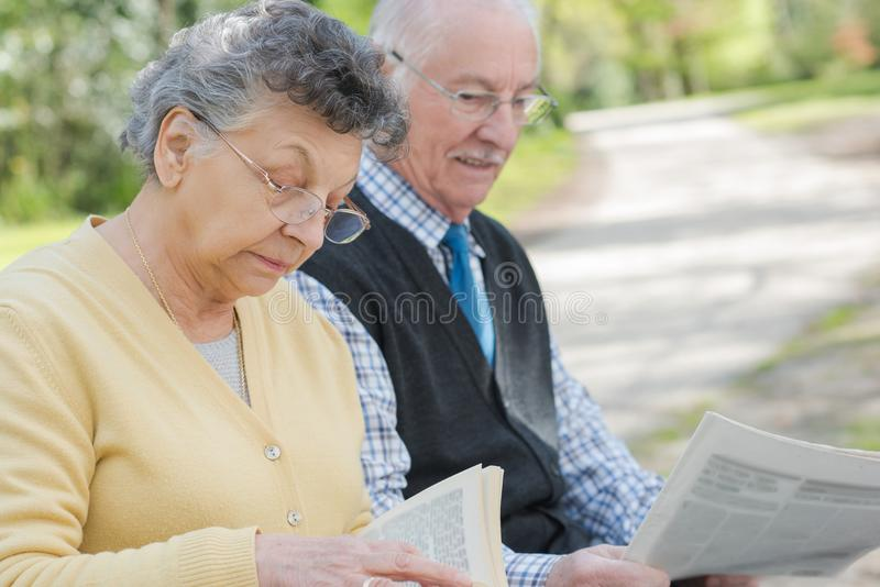 Periódico maduro feliz de la lectura de los pares al aire libre imagenes de archivo