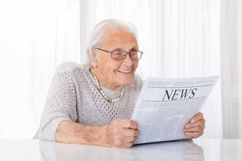 Periódico mayor de la lectura de la mujer imágenes de archivo libres de regalías