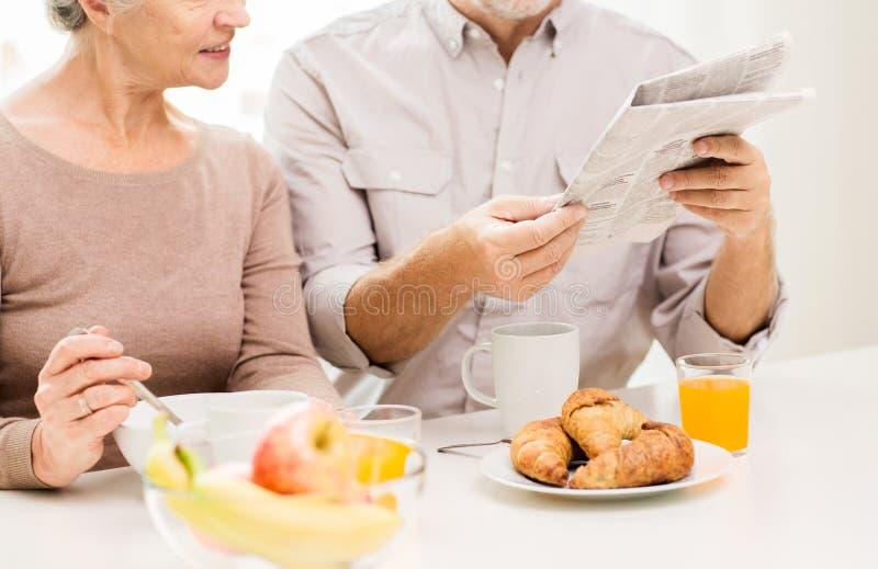 Periódico mayor feliz de la lectura de los pares en el desayuno imágenes de archivo libres de regalías