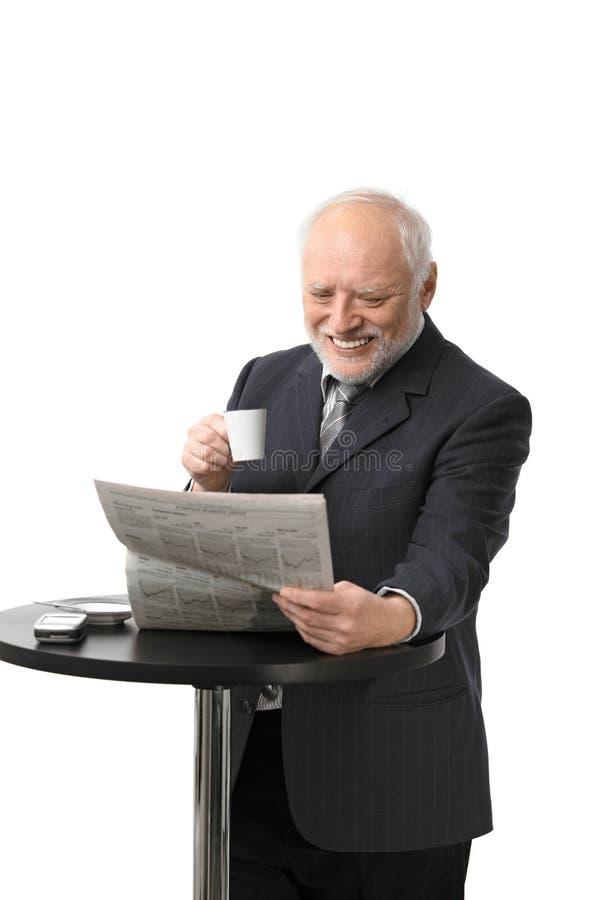 Periódico mayor feliz de la lectura del hombre de negocios imágenes de archivo libres de regalías