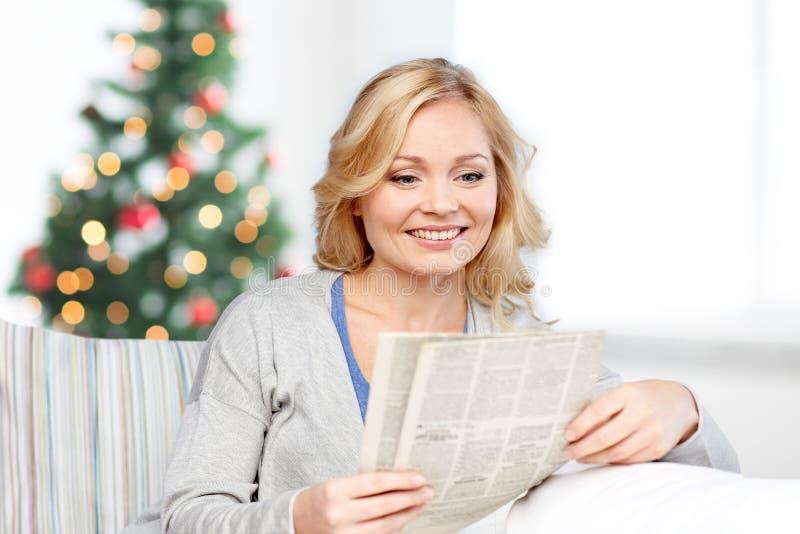 Periódico sonriente de la lectura de la mujer en la Navidad fotos de archivo