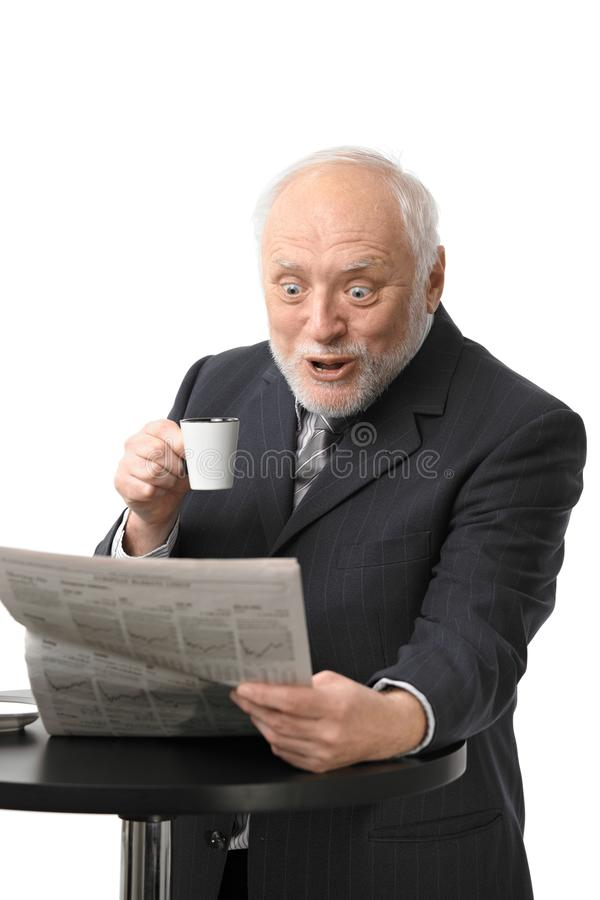 Periódico sorprendido de la lectura del hombre de negocios foto de archivo