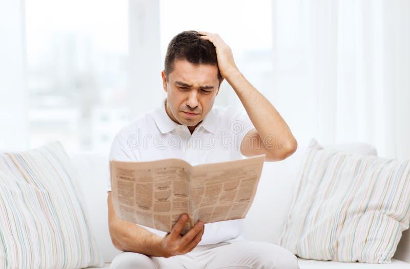Periódico triste de la lectura del hombre en casa imagenes de archivo