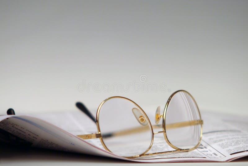 Periódico y vidrios fotos de archivo libres de regalías