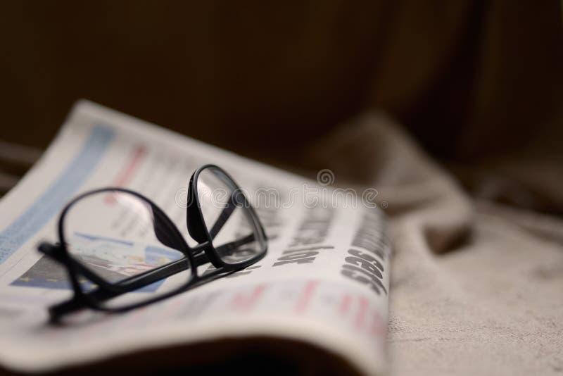 Periódico y vidrios fotografía de archivo