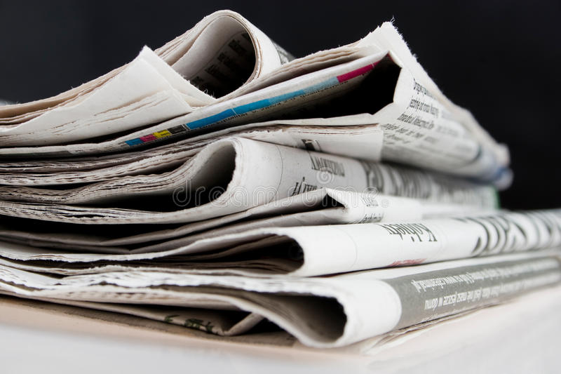 Periódicos en fondo negro imagenes de archivo