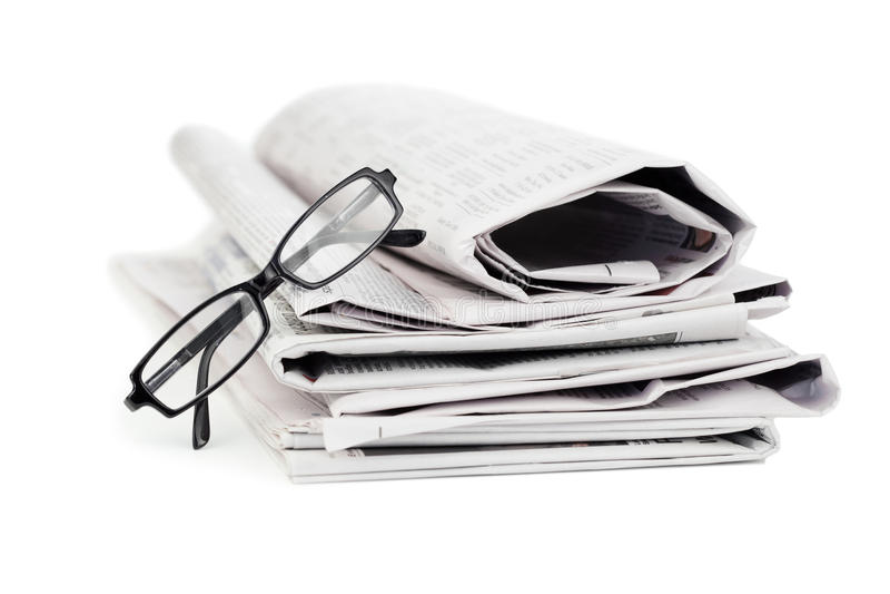 Periódicos y vidrios negros imagen de archivo