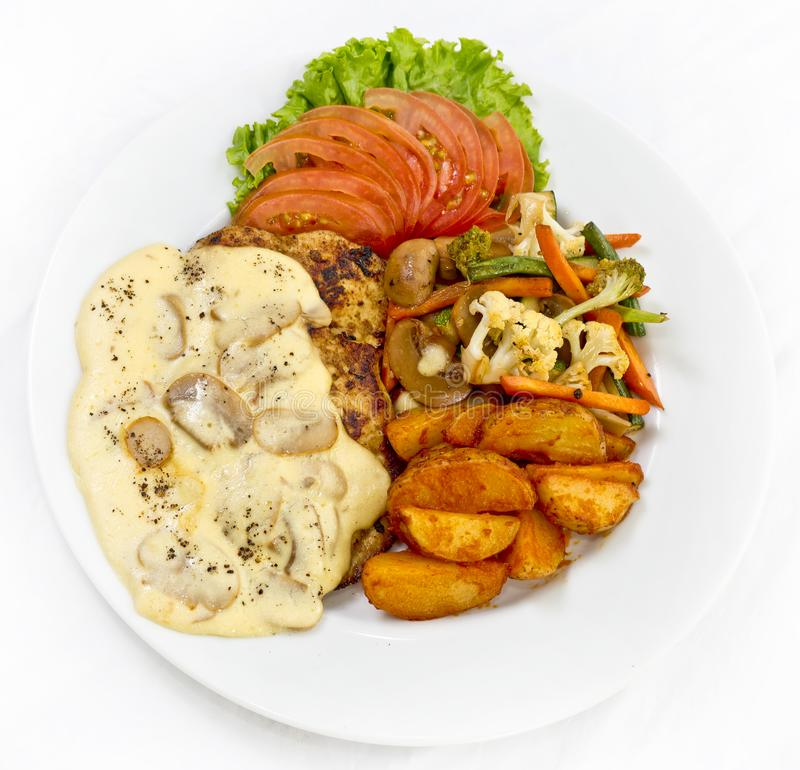 Peri peri Chicken with Button mushroom gravy, Saute Vegetables, Spicy fried Potatoes with Tomato Lettuce Salad.  stock photos