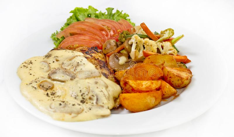 Peri peri Chicken with Button mushroom gravy, Saute Vegetables, Spicy fried Potatoes with Tomato Lettuce Salad.  stock images
