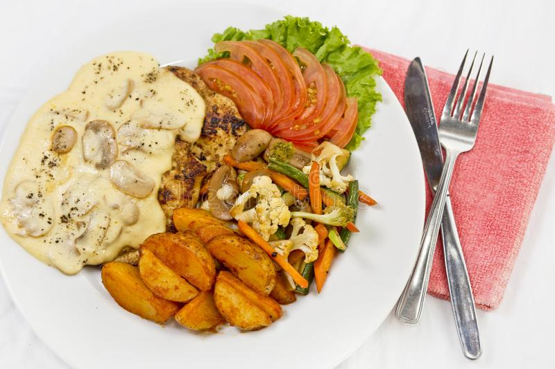 Peri peri Chicken with Button mushroom gravy, Saute Vegetables, Spicy fried Potatoes with Tomato Lettuce Salad.  royalty free stock photography