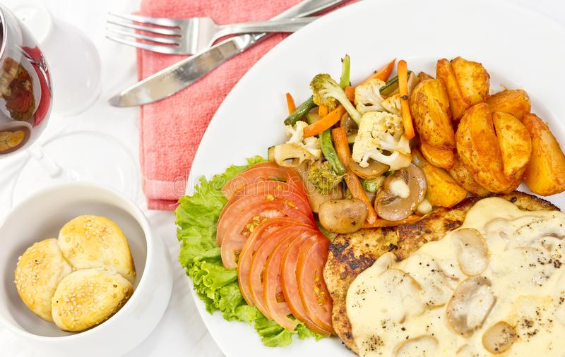 Peri peri Chicken with Button mushroom gravy, Saute Vegetables, Spicy fried Potatoes with Tomato Lettuce Salad.  stock photography