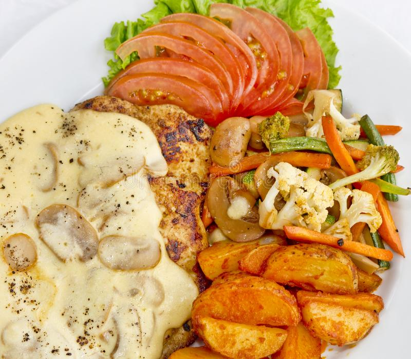 Peri peri Chicken with Button mushroom gravy, Saute Vegetables, Spicy fried Potatoes with Tomato Lettuce Salad.  royalty free stock image