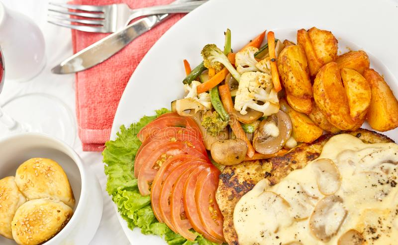 Peri peri Chicken with Button mushroom gravy, Saute Vegetables, Spicy fried Potatoes with Tomato Lettuce Salad.  royalty free stock images