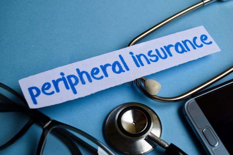 Perifer försäkringinskrift med sikten av stetoskopet, glasögon och smartphonen på den blåa bakgrunden arkivfoto