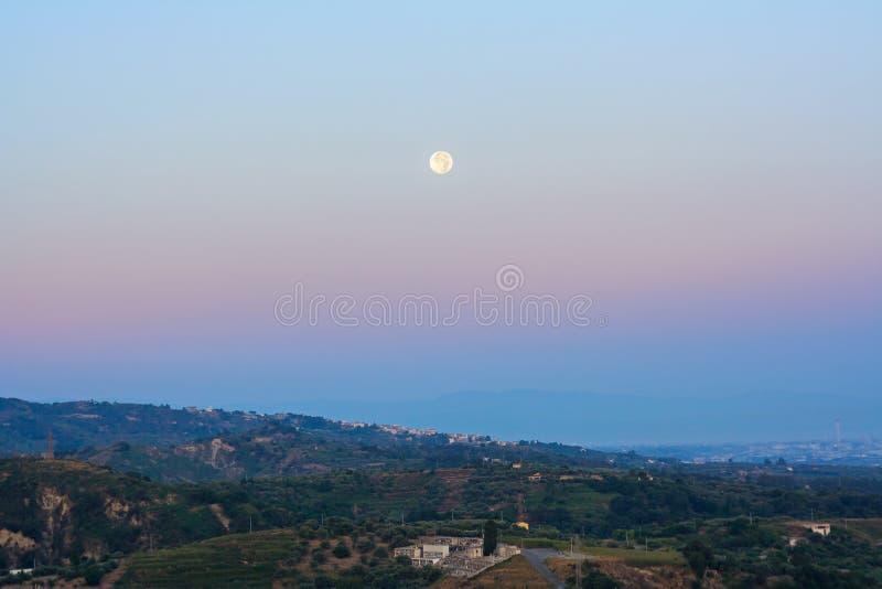 Perigeo della luna piena durante l'alba in Sicilia immagini stock