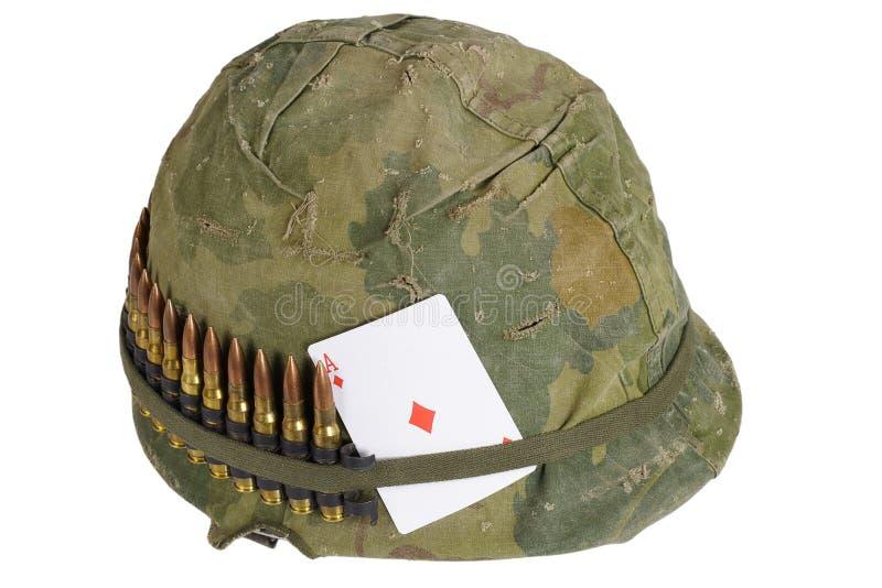 Period för vietnamkriget för hjälm för USA-armé med kamouflageräkningen, ammobältet och amuletten som spelar kortöverdängaren av  arkivfoto
