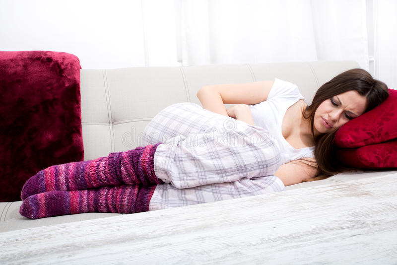 Period pain. Young woman in the sofa with period pain stock photography