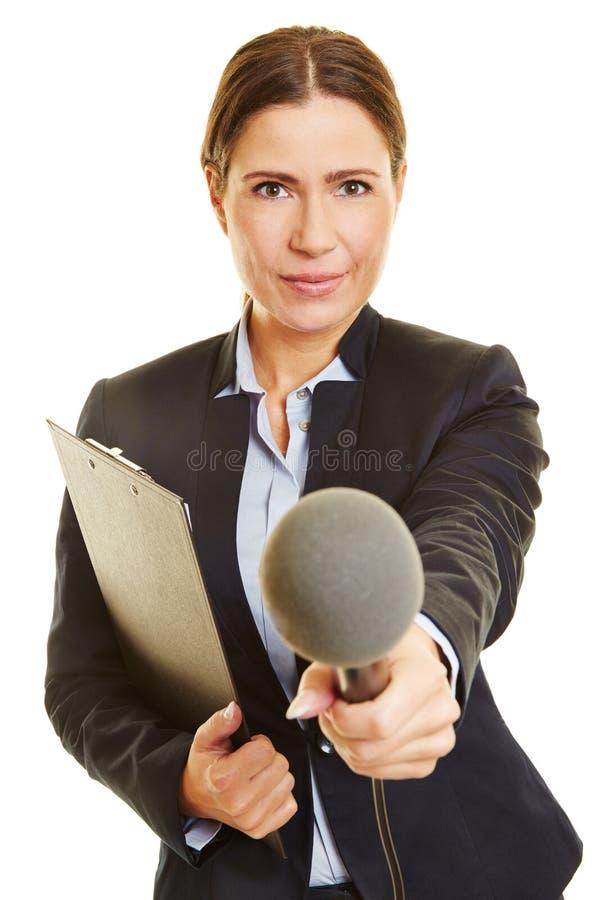 Periodista con el micrófono que hace entrevista de la encuesta fotografía de archivo