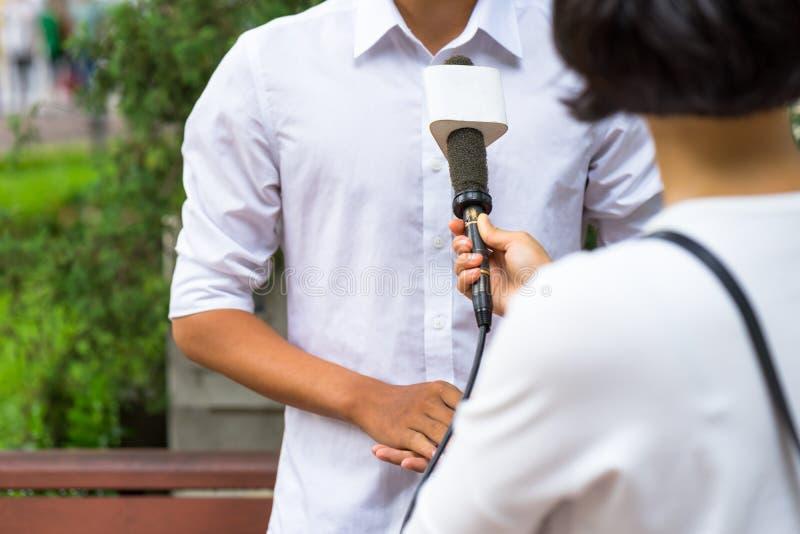 Periodista de las noticias con el micrófono que se entrevista con en el primer de la calle imagen de archivo