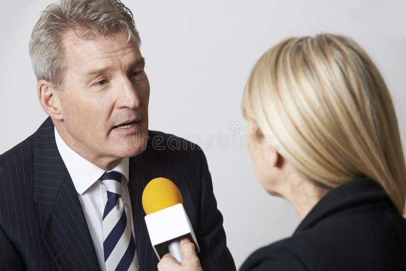 Periodista de sexo femenino With Micropho de Being Interviewed By del hombre de negocios fotos de archivo