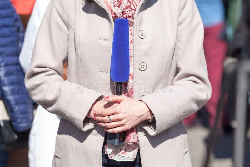 Periodista de sexo femenino que sostiene el micrófono, divulgando en un evento mediático fotografía de archivo libre de regalías