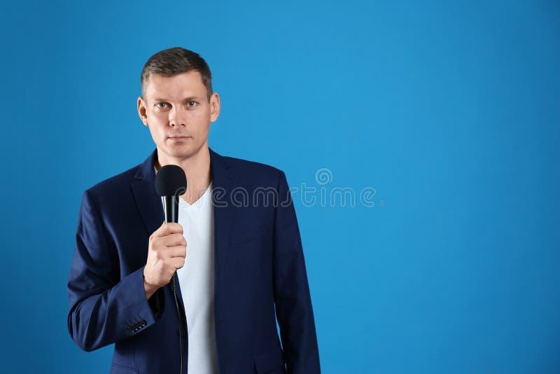 Periodista masculino con micrófono en azul Espacio para texto fotos de archivo