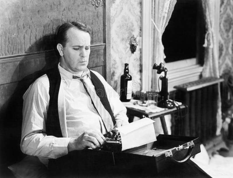 Periodista que se sienta en su cama con una máquina de escribir, mecanografiando (todas las personas representadas no son vivas m imagen de archivo