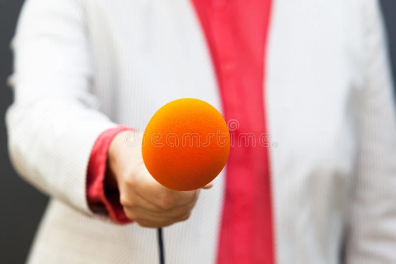 Periodista que sostiene el micrófono, haciendo entrevista de los medios imagenes de archivo