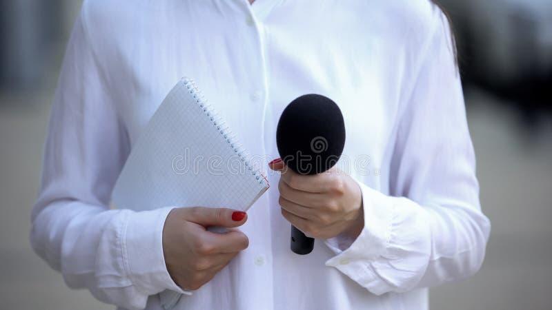 Periodista sosteniendo un cuaderno y micrófono, preparándose para la entrevista foto de archivo