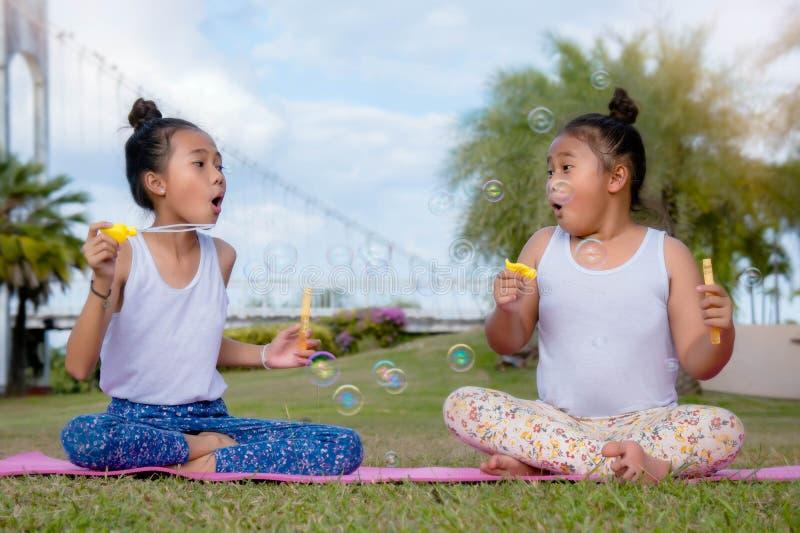 Periodo felice di amicizia, bolla di sapone del gioco della sorella del bambino di due ragazze Smil immagini stock