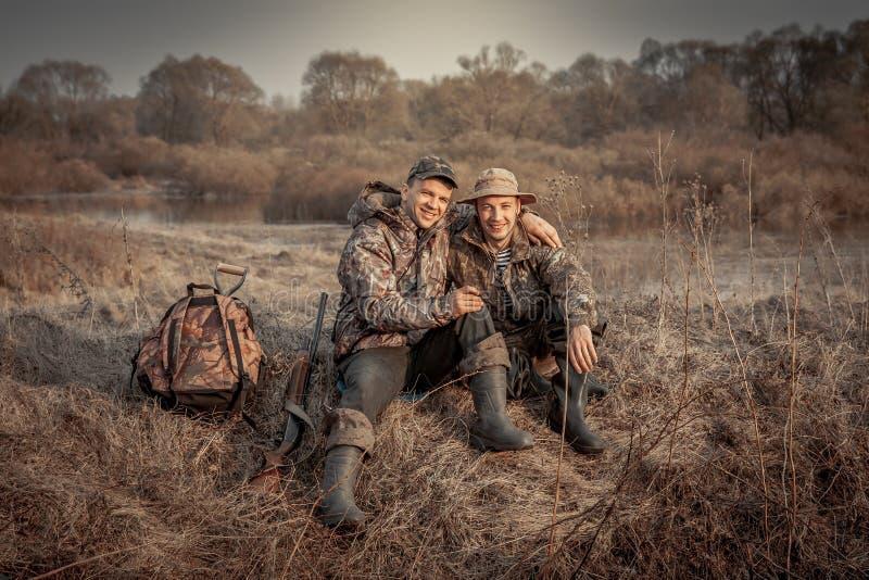 Periodo rurale di caccia del campo di ricreazione degli amici degli uomini del cacciatore che simbolizza forte amicizia immagine stock libera da diritti