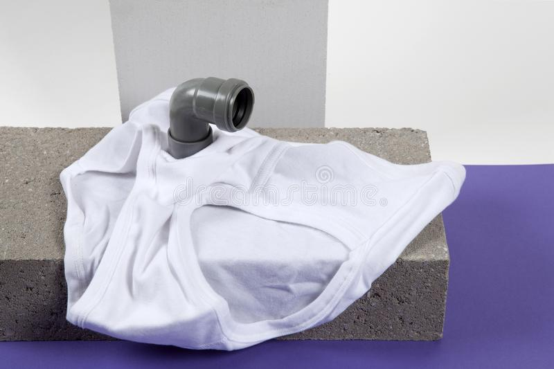 Periscope y fronts violet. A metaphor of periscope made with pipes emerging from a y-front male underwear on cinder block. Violet and white backgroud. Minimal royalty free stock photography