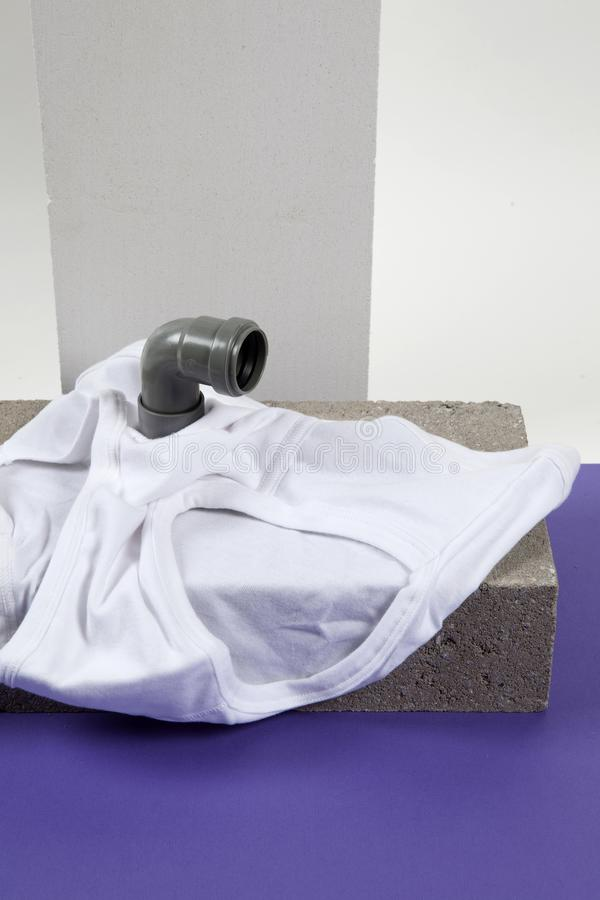 Periscope y fronts violet. A metaphor of periscope made with pipes emerging from a y-front male underwear on cinder block. Violet and white backgroud. Minimal stock images