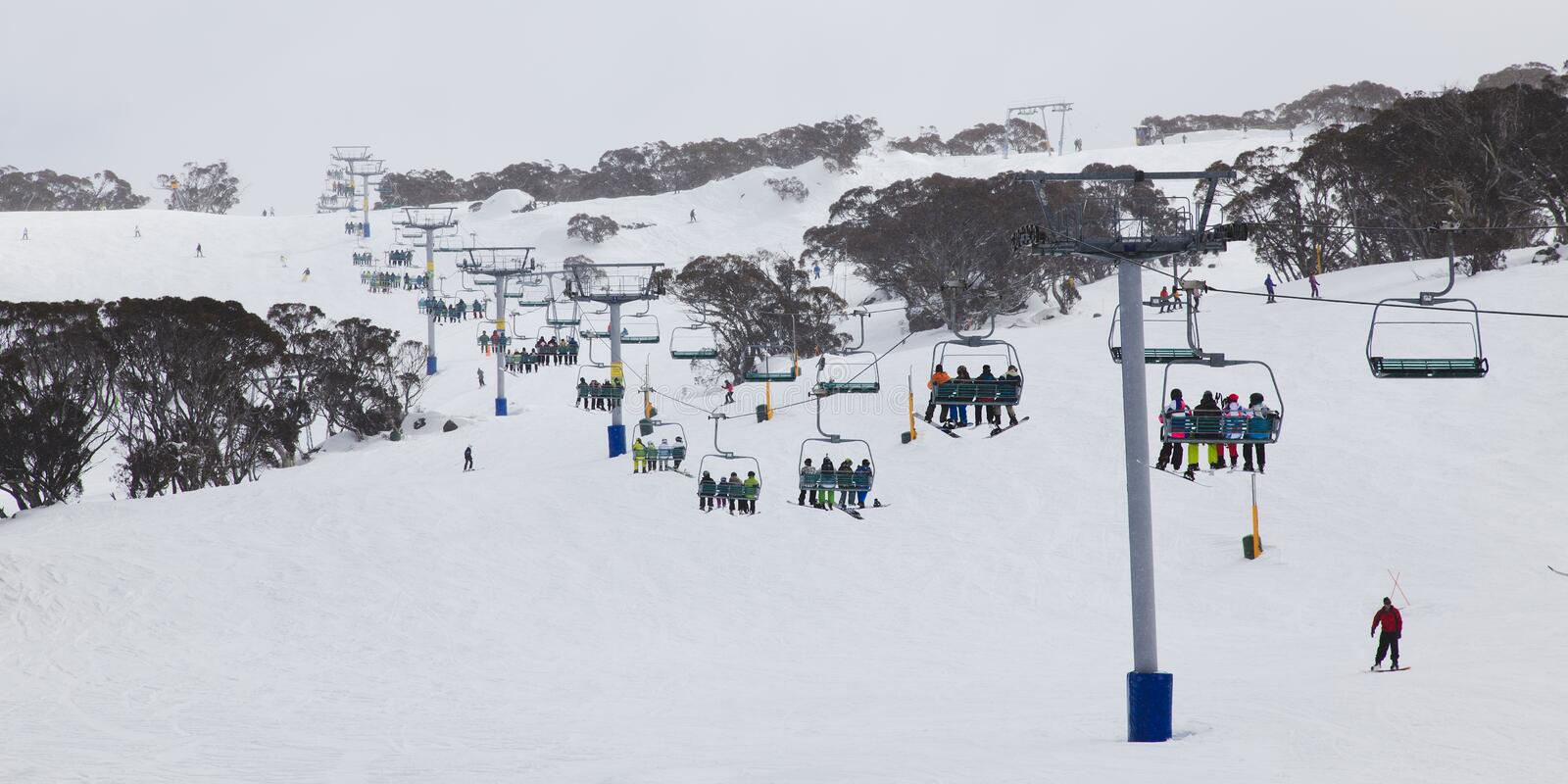 Perisher 8 chair lift pan. Ski resort 8 chair lift up to the mountains in winter with whitу snow and skiying people stock photos