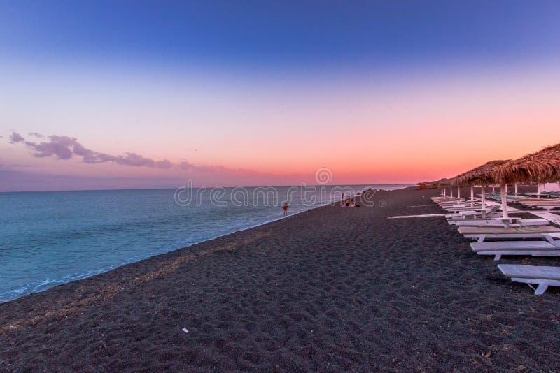 Perissa, playa en la puesta del sol, Santorini, Grecia con las chozas hermosas de la playa, el cielo azul y las nubes imagen de archivo libre de regalías