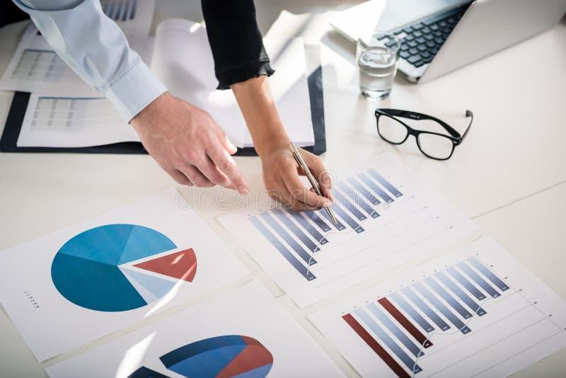 Peritos do negócio que analisam a barra e gráfico de setores circulares estatísticos foto de stock royalty free