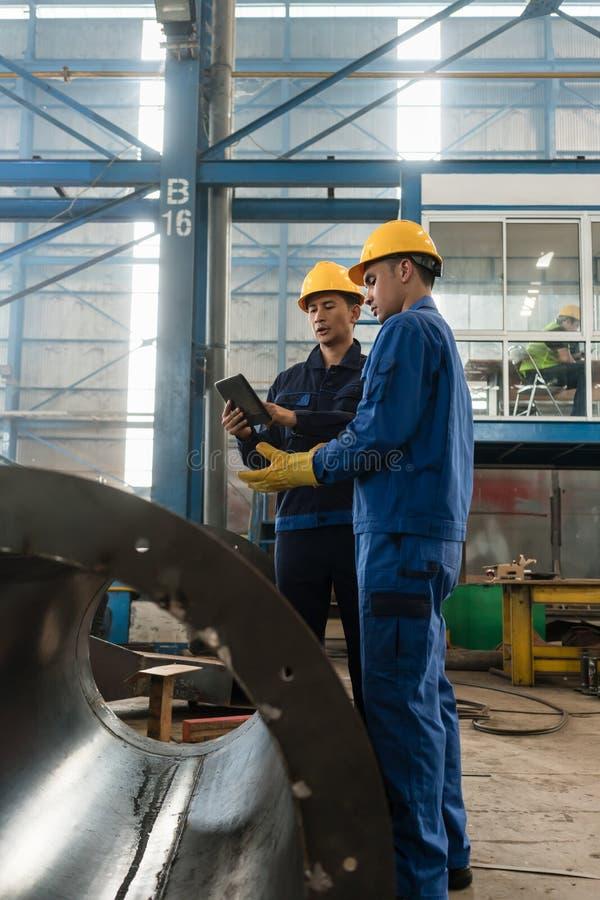 Peritos que verificam a informação no PC da tabuleta em uma fábrica moderna fotos de stock